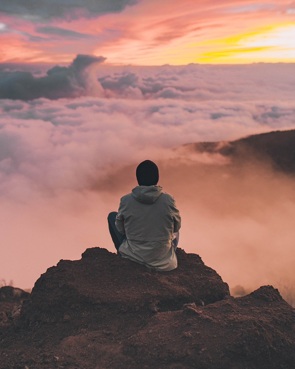 Man in a hat sitting on a rock overlooking clouds at sunset practicing meditation in Denver CO. Our caring therapists can help you learn mindfulness at Catalyss Counseling in Englewood CO 80209 and 80210