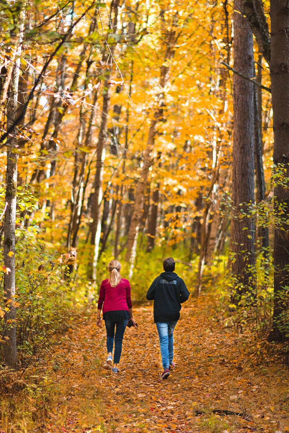 A new mom walking with a friend on a path in nature to help combat isolation in Denver CO. Our caring and compassionate therapists at Catalyss Counseling can help you feel less alone and more connected postpartum in Englewood CO 80209 and 80210
