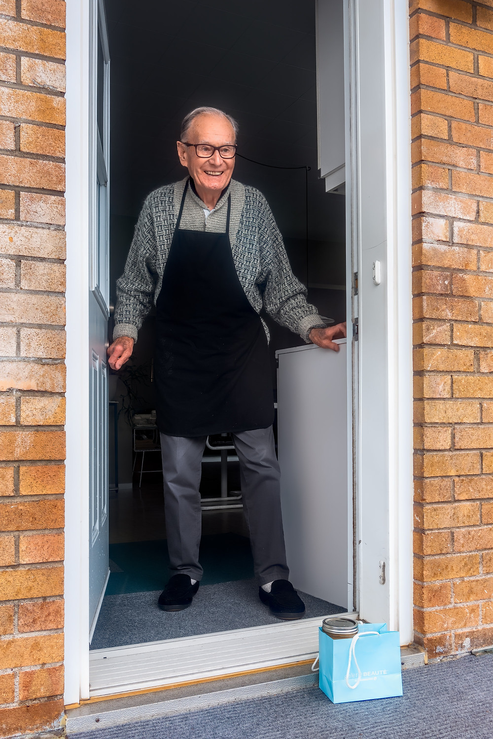 Older man with an apron opening his front door with a bag of food that his neighbor brought him as a way of giving back in Denver CO. Catalyss Counseling can help you rediscover your purpose if you are a helper through therapy in Englewood CO 80209 and 80210