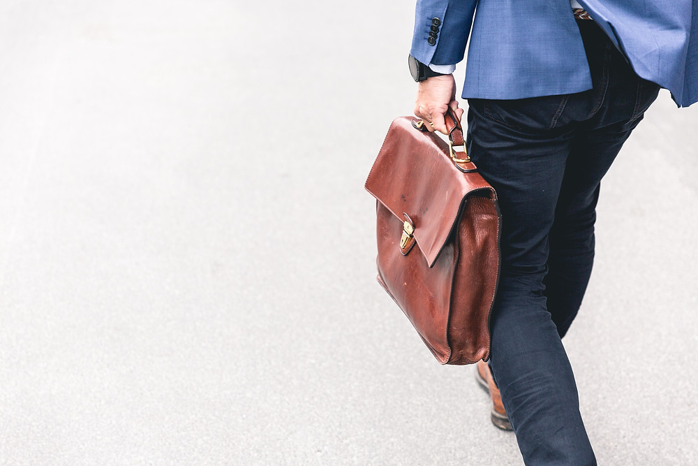 Man with a red briefcase walking home from work so he can spend time with his family in Denver CO. We can help you treat your stress and balance your life again through therapy with Catalyss Counseling in Englewood CO 80209 and 80210