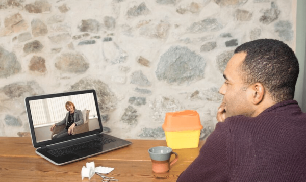 Man of color sits at desk across from laptop while engaged in online therapy in Colorado through Catalyss Counseling. We provide convenient and secure online therapy to the Denver area and beyond.