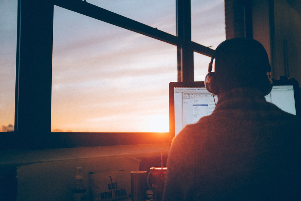 Man sitting at a desk doing online counseling from his home in Englewood CO using headphones and a laptop computer to talk to his therapist, also looking at a sunset out the window. Man getting convenient counseling online in the Denver CO area with Catalyss Counseling 80209 and 80210