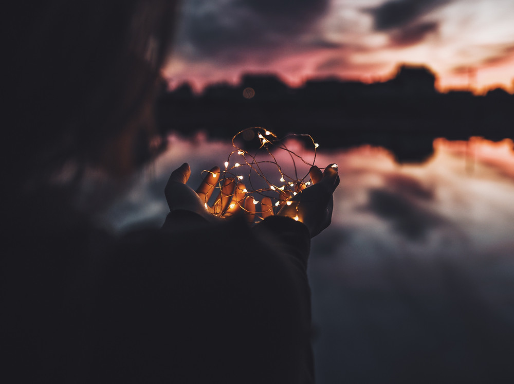 Hands holding a tangle of lights with a sunset background in Colorado. Signifying that one's brain can be changed through EMDR treatment for trauma in Englewood CO. You can get help for your trauma and anxiety by getting EMDR treatment in Denver CO 80209 and 80210