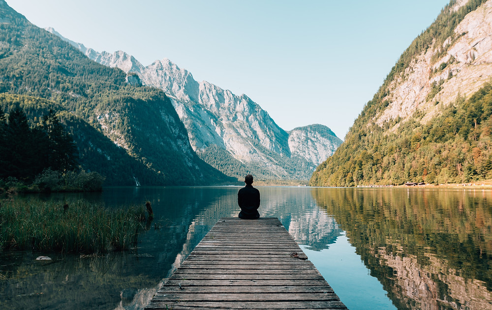 Practicing mindfulness and feeling calm, a person sits on a dock overlooking a lake with mountains in the background in Denver CO. Feeling calm after getting treatment for anxiety and practicing mindfulness in Englewood CO by Catalyss Counseling 80209 and 80210