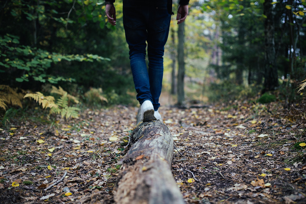 Person walking on a log on a forest with white shoes trying to balance work and life in Englewood CO. We can help you balance your life by empowering change through counseling in Denver CO 80209 and 80210