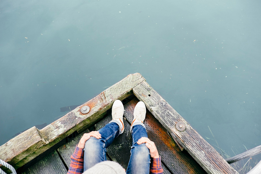 Overhead view of person sitting on corner of a boat dock and water.