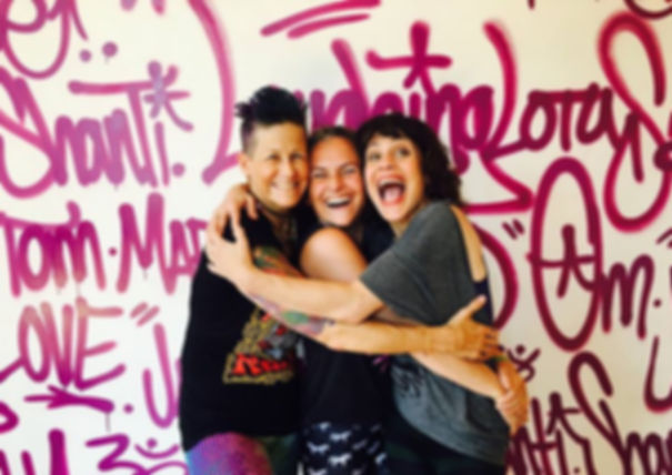 Three hugging women in front of a graffiti wall