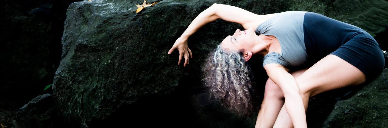 Frau in yoga pose leaning against huge rocks in central parl, nyc