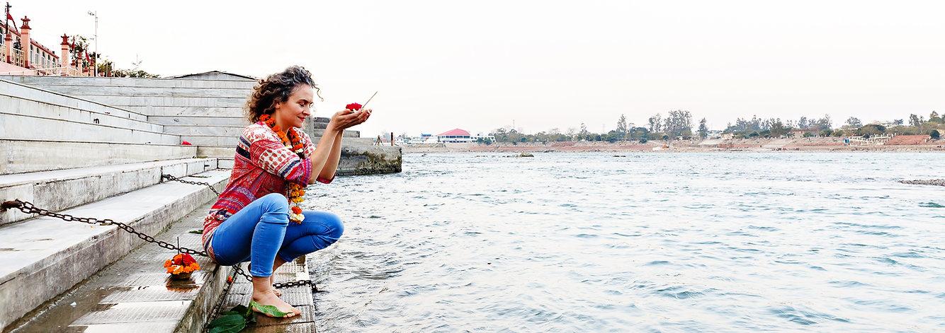 Praying yogi besides Ganga River in Rishikesh, India