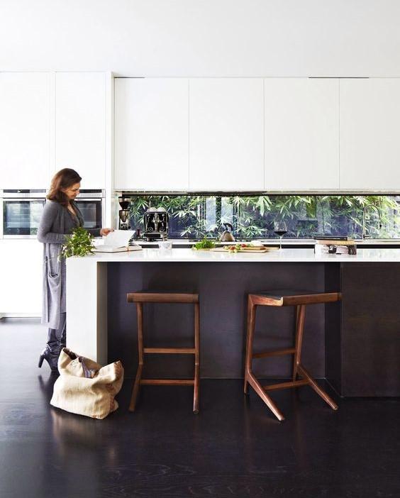 Keittiön peräseinä on kokonaan ikkunaa. Se antaa sisustukselle uuden ulottuvuuden.