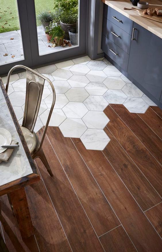 Keittiön ulko-oven edusta on laatoitettu kuusikulmaisilla marmorilaatoilla. Laatoitus loppuu epäsymmetrisesti ja laatat jatkuvat tummana parkettina.