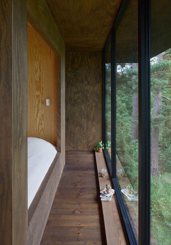 Mökin makuuhuoneen seinä on lattiasta kattoon ikkunaa.