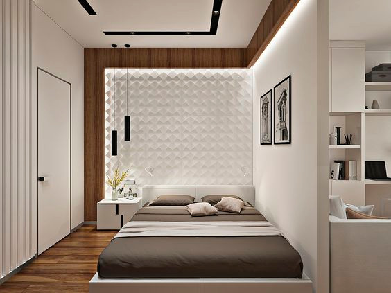Sänky on sijoitettu epäsymmetrisesti seinän viereen. Tausaseinälle on rajattu alue 3d laatoista, jotka on valaistu.