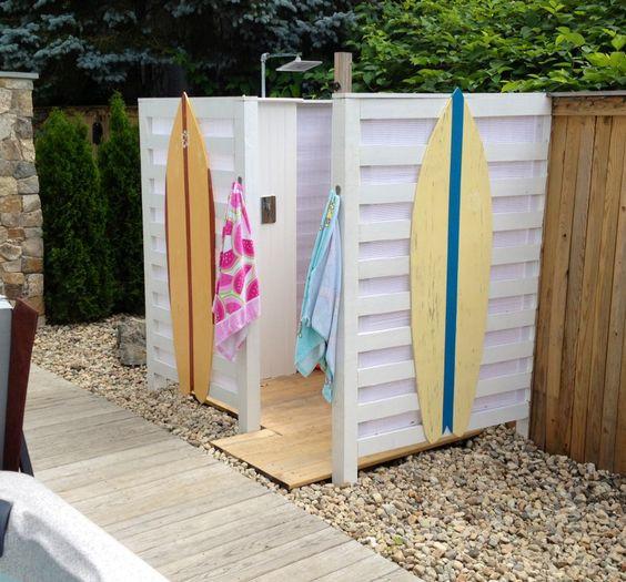 Surffiteema on tuotu ulkosuihkuun kiinnittämällä surffilaudat suihkun ulkoseiniin ja levittämällä pieniä koristekiviä suihkukopin ympärille.