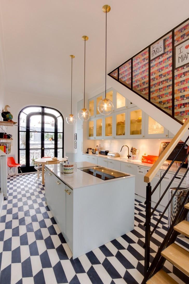 Upeasta mustavalkoisesta kaari-ikkunasta tulvii valoa keittiöön. Portaiden alla olevien kaappien lisäksi keittiötila jatkuu myös edessä olevalla saarekkeella. Tasot ovat valkoista marmoria ja kaappien vetimet sekä lamppujen yksityiskohdat kultaisia. Portaiden askelmat ja kaiteen käsipuu on vaaleaa puuta ja muut osat mustaa metallia.
