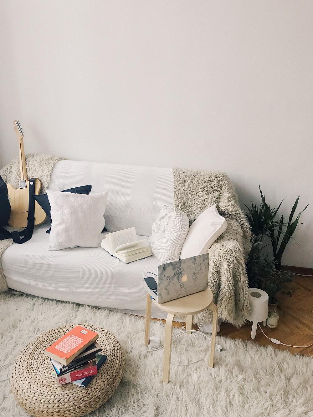 Bogeemissa olohuoneessa on hieman beigeen vivahtava valkoinen seinä ja puhtaanvalkoinen sohva.