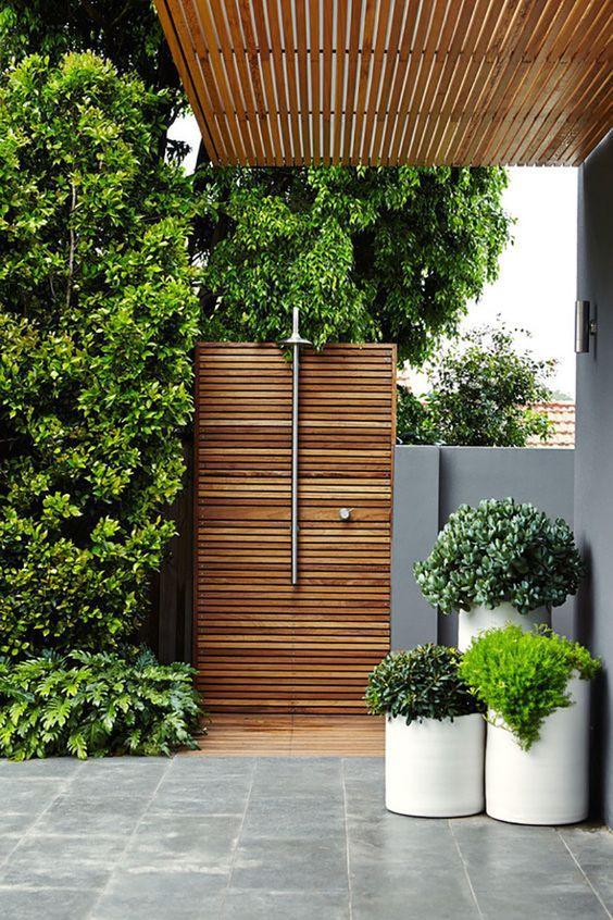 Poikittaisesta puurimoituksesta on tehty suihkun taustaseinä ja lattia. Se on yksinkertainen ja moderni. Puu on käsitelty lämpimän oranssilla sävyllä ja se sopii harmaaseen rakennukseen ja muuriin jonka vieressä suihku sijaitsee.