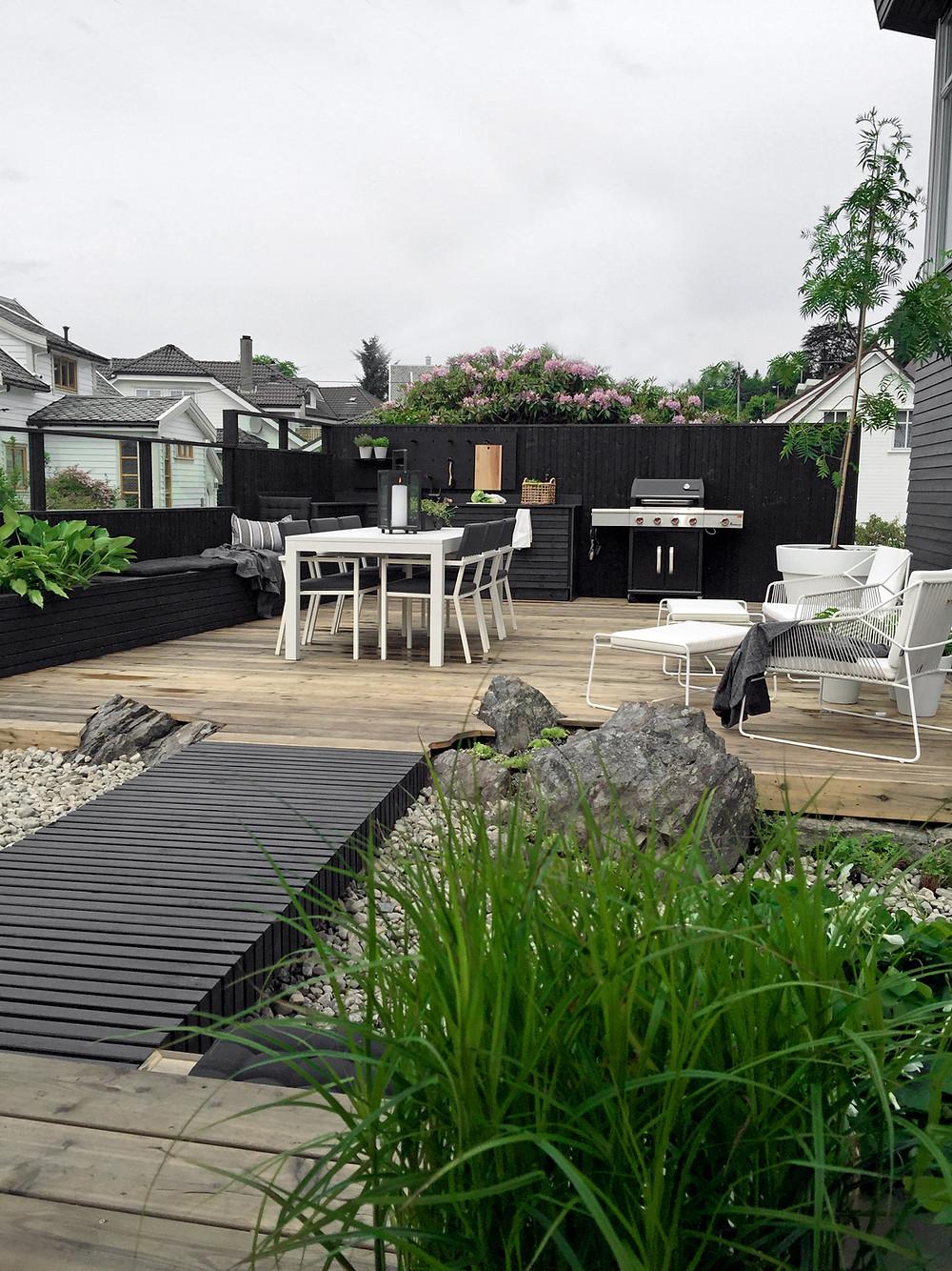 Terassialueen laidoille on takennettu musta korkea aita, joka toimii taustana kesäkeittiölle sekä selkänojana penkeille, mutta myös suojaa naapureiden katseilta.