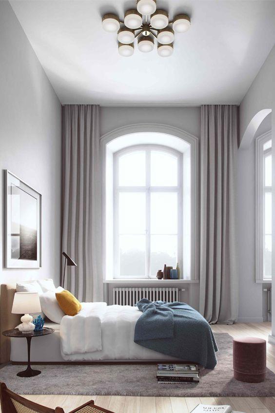 Kaari-ikkunan molemmille puolille on sijoitettu vaaleanharmaat verhot jotka ylettyvät lattiasta kattoon.