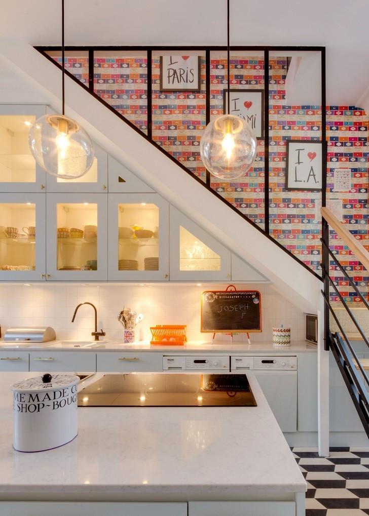 Portaiden alapuolella on valkoinen keittiö. Portaiden mustat yksinkertaiset metallikaiteet sopivat lattian mustavalkoiseen laatoitukseen. Portaiden takaseinän värikäs tapetti tuo keittiötilaan väriä. Keittiökaapit on sijoitettu portaiden alle.