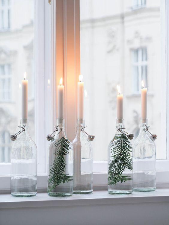 Lasipullojen sisään on laiettu kuusenoksa ja pullojen suuhun valkoiset kynttilät palamaan.