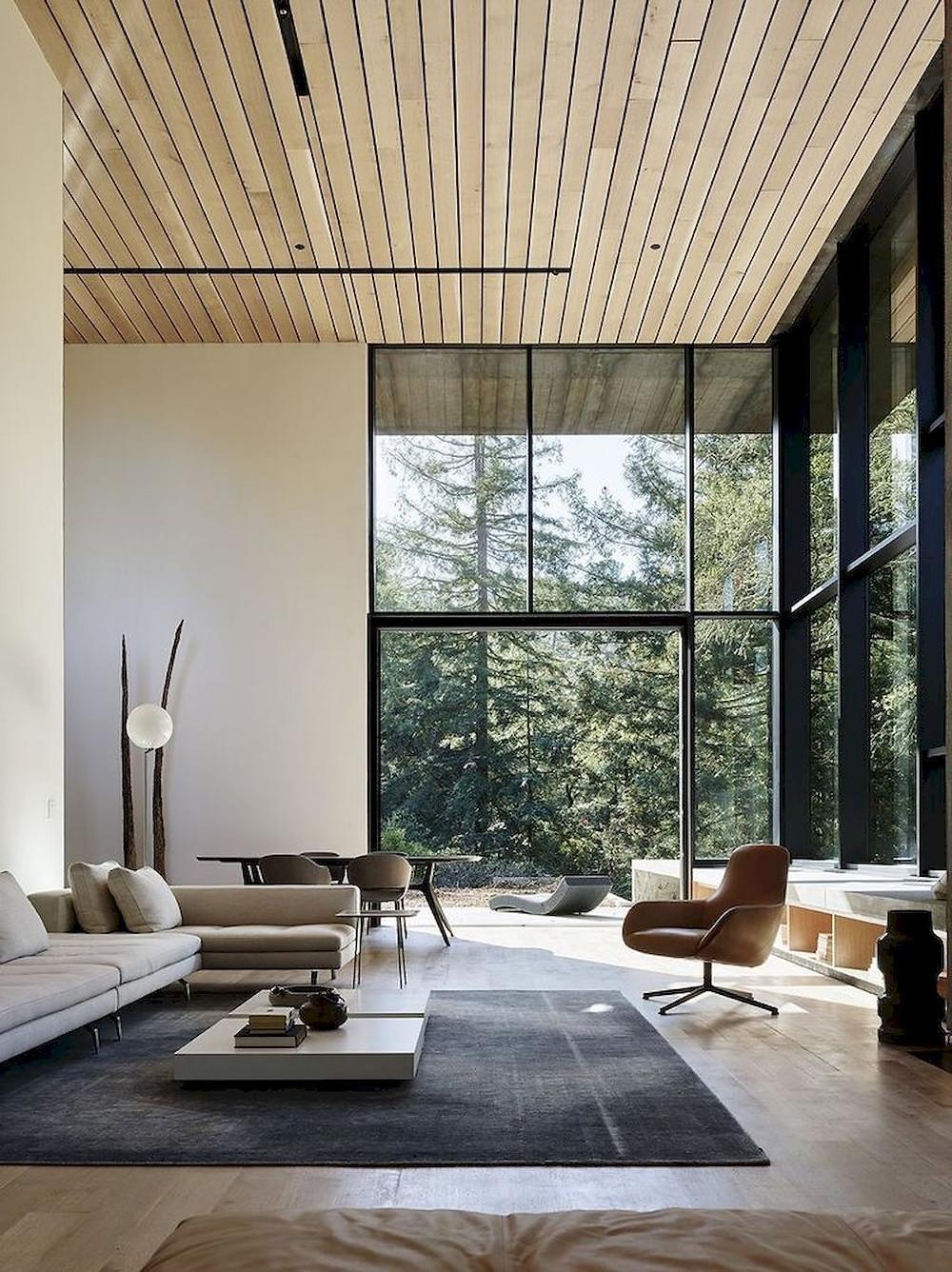 Modernissa korkeassa olohuone-ruokailutilassa on ikkunat lattiasta kattoon.