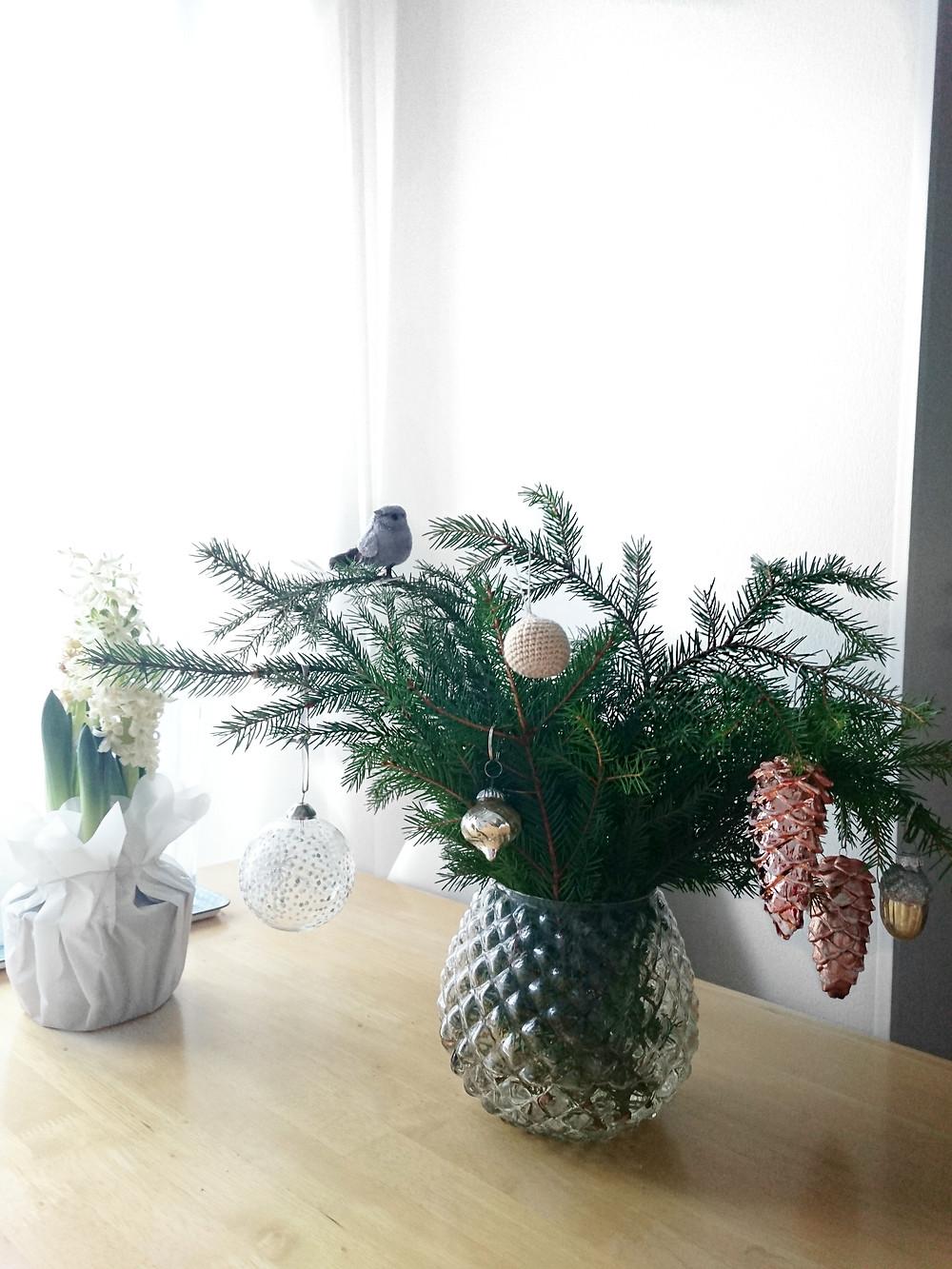 Kuusenoksia on kerätty maljakkoon ja oksiin on ripustettu muutamia joulukoristeita.