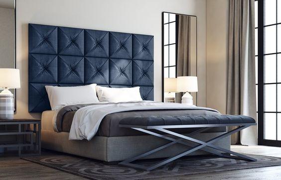 Sängyn taakse on laitettu korkea tummansininen sängynpääty. Se tuo hieman väriä muuten ruskean sävyiseen sisustukseen.