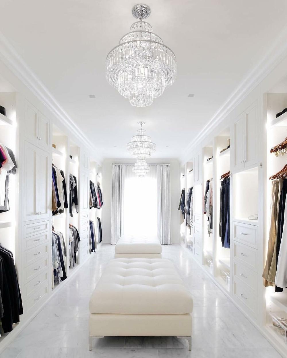 Valkoista vaatehuonetta koristaa keskellä kaksi kattokruunua sekä nahkaiset rahit, joissa voi istua pukeutuessaan.