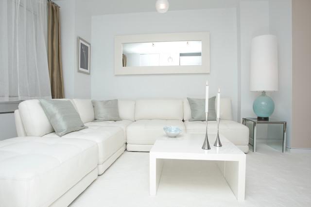 Olohuoneessa lattia, sohva, sohvapöytä, peili, toinen verho sekä lampunvarjostin ja seinä ja kattopinnat ovat valkoiset. Sohvalla on vain kolme harmaata tyynyä ja lampunjalka on turkoosi sekä pöydällä olevassa pienessä kulhossa on hieman sinistä.