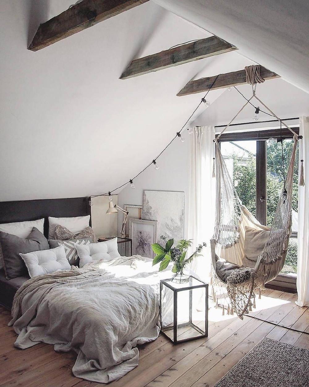 Harjakattoisessa makuuhuoneessa on boheemi tunnelma. Tummat puiset kattopalkit on jätetty näkymään. Palkista roikkuu valkoinen riipputuoli. Kolme taulua on jätetty seinää vasten sommitelmaksi.