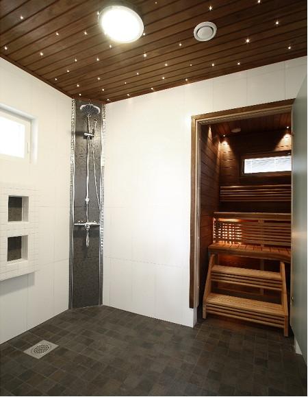 Kylpyhuoneen katto ja lattia ovat tummanruskeat ja seinät valkoiset. Tämä saa huoneen tuntumaan ahtaalta ja tunkkaiselta ja näyttää kuin katto romahtaisi niskaan.