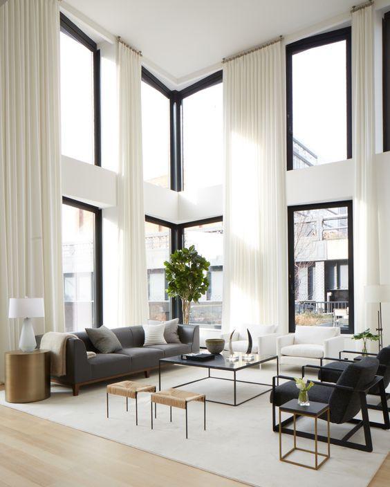 Isossa ja korkeassa olohuoneessa on laitettu valkoiset verhot lattiasta kattoon asti. Verhot ovat riittävän leveät isoon tilaan.