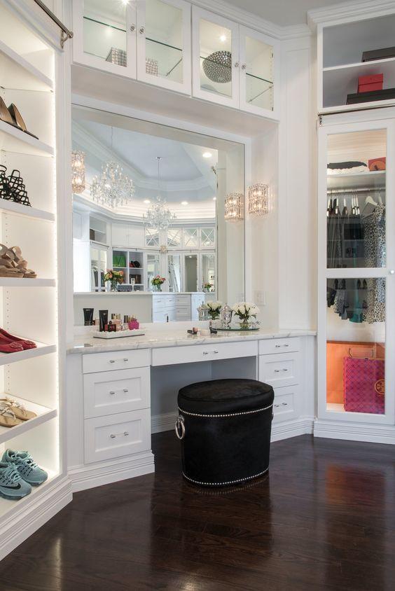 Valoisassa vaatehuoneessa valkoiset kaapistot yhdistyvät tummaan puiseen lattiaan. Meikkauspiste on rakennettu kiinteäksi. Jättimäinen peili yltää meikkauspöydän päästä päähän. Pöydän marmoritaso sopii vaatehuoneen moderniin ilmeeseen.