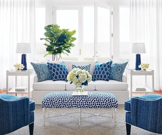 Valkoiseen olohuoneeseen on laitettu rohkeasti sinistä mukaan. Valkoiselta sohvalta löytyy sinisiä kuviollisia tyynyjä ja vastapäätä olevat kaksi nojatuolia ovat sinisiä. Sohvapöytä on valkoinen sinisillä eläimellisillä pilkuilla.