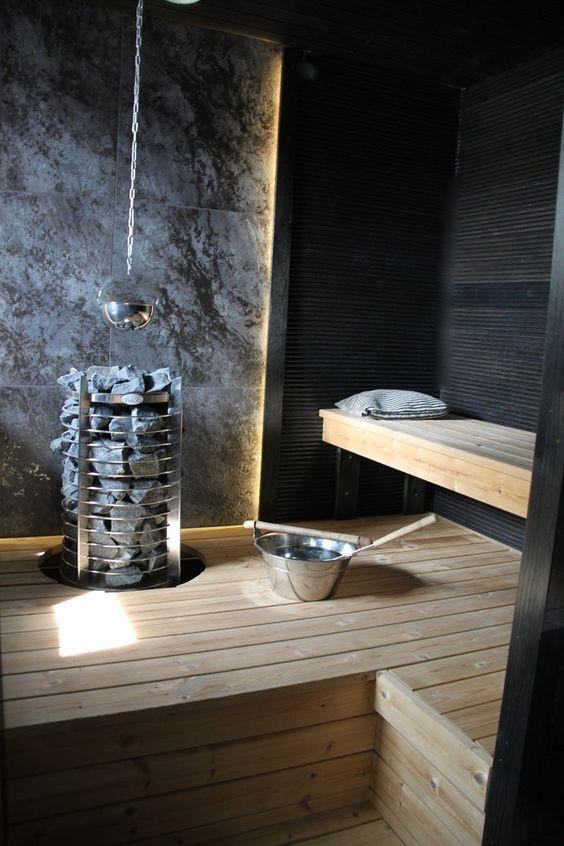 Saunan musta somipaneelinen seinä ja vaaleat lauteet luovat hienon kontrastin. Kiukaan takaseinässä on käytetty leveää kivikuvioista laattaa ja se on valaistu epäsuorasti LED-nauhalla.