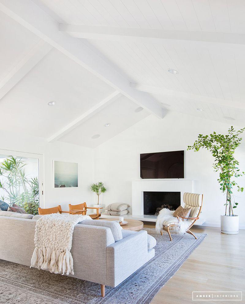 Vaaleassa harjakattoisessa olohuoneessa harmaa kuviollinen matto rajaa oleskelutilan. Sohva, nojatuolit ja pyöreä puinen sohvapöytä on sijoitettu maton päälle.