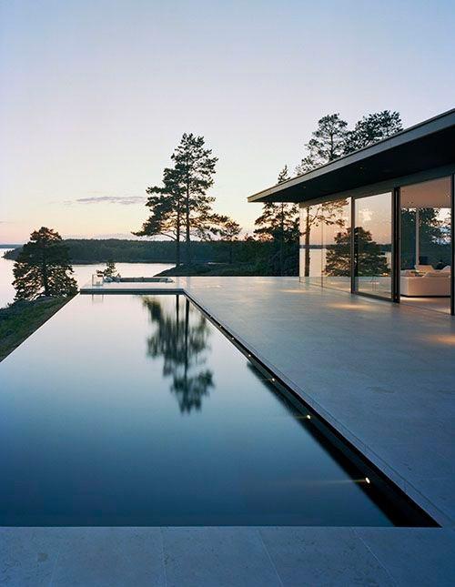 Moderni uima-allas on valaistu seinistä. Yksinkertainen allas sopii suomalaiseen järvimaisemaan.