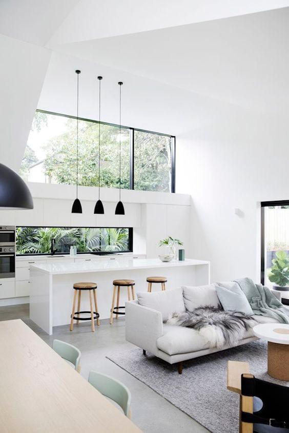 Modernissa keittiössä välitilaan on koko matkalta laitettu ikkuna. Keittiön yläkaappien päällä on myös valtava ikkuna joka ylettää kattoon asti.