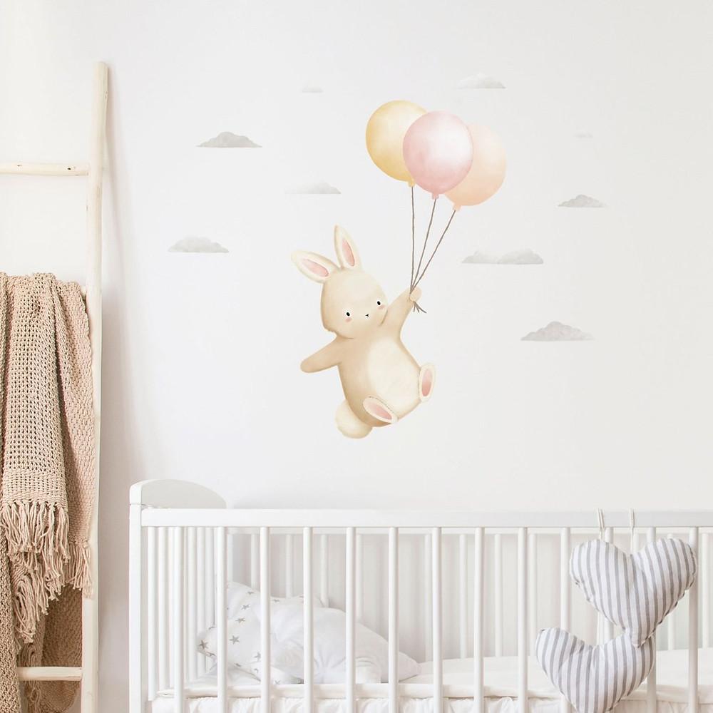 Seinätarrassa pupu leijailee kolmen ilmapallon kanssa pilvien keskellä.