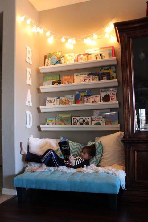 Lapselle on tehty lukunurkkaus kiinnittämällä seinälle neljä tauluhyllyä ja laitettu niihin kirjoja. Hyllyjen alle on tehty löhöily paikka.