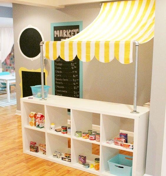 Ikean Kallax hyllystä on rakennettu leikkikauppa pienelle lapselle kiinnittämällä siihen kiinni markiisikangas.