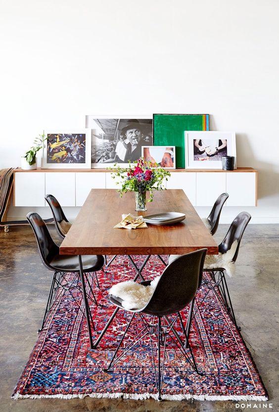 Ruokapöydän alla on matto. Tuolit hädintuskin mahtuvat maton alle koska matto on liian pieni.