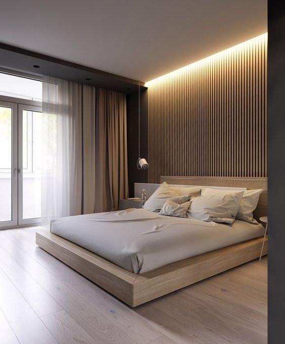 Sängyn päätyseinään on tehty pystyrimoitus puusta. Sitä korostaa ylhäältä tuleva valaistus.