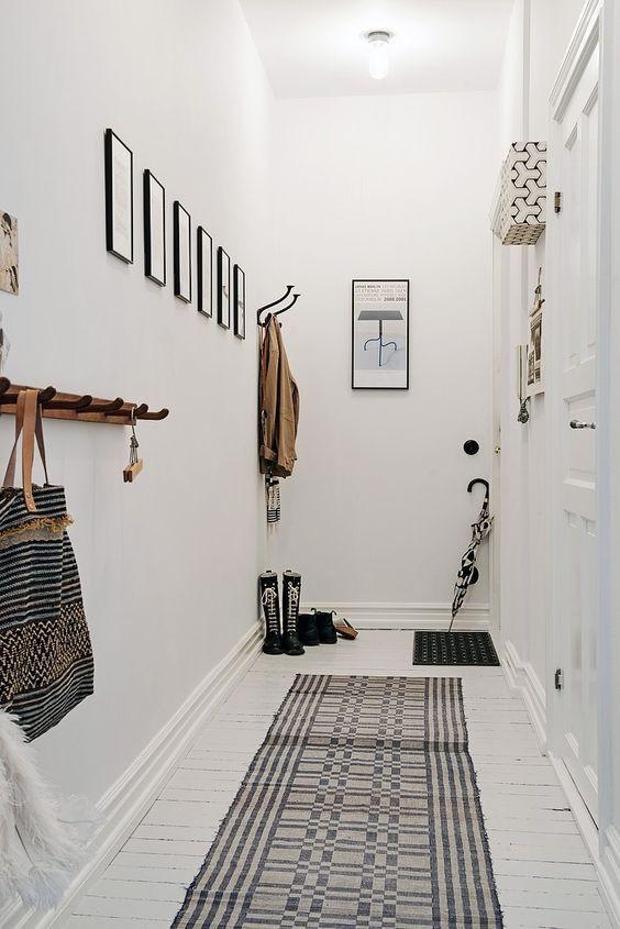 Valkoisen pitkän eteisen seinille on ripustettu sinne tänne tauluja ja koukkuja. Lattialta löytyy kaksi pientä mattoa toinen oven edestä ja toinen käytävämatto.