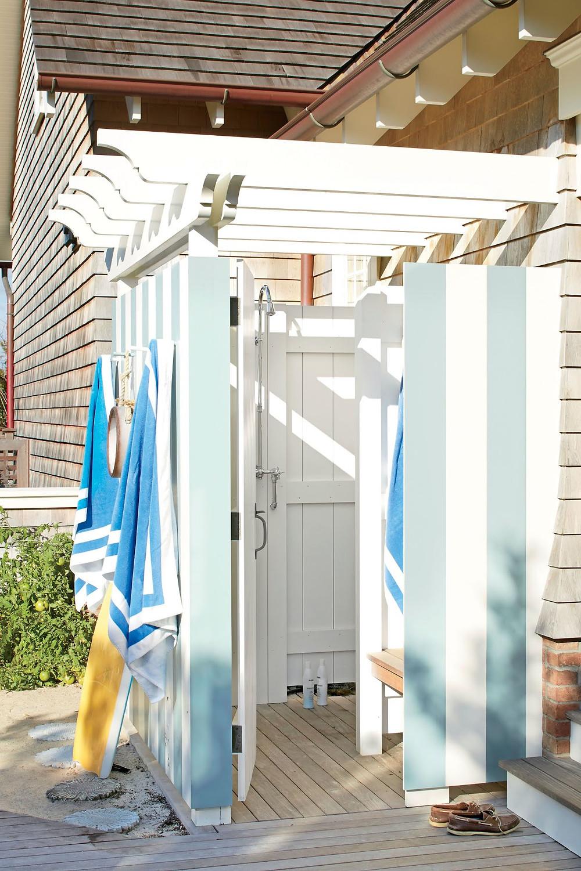 Söpö suihkukoppi on maalattu hempeän vaaleansinisellä sekä valkoisella maalilla pystyraitoja.