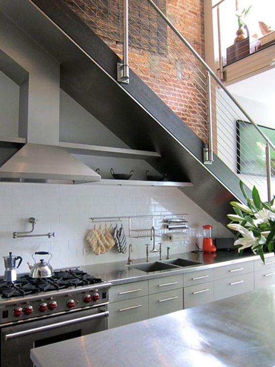 Harmaa moderni keittiö on rakennettu portaiden alle.