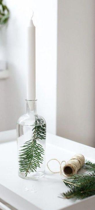 Lasipullon sisälle on laitettu vettä ja kuusenoksa. Lasipullon suussa on valkoinen kruunukynttilä.