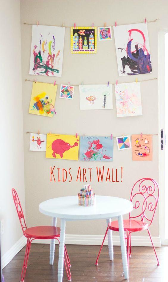 Seinälle on kiinnitetty naruja joihin piirustukset saa roikkumaan.