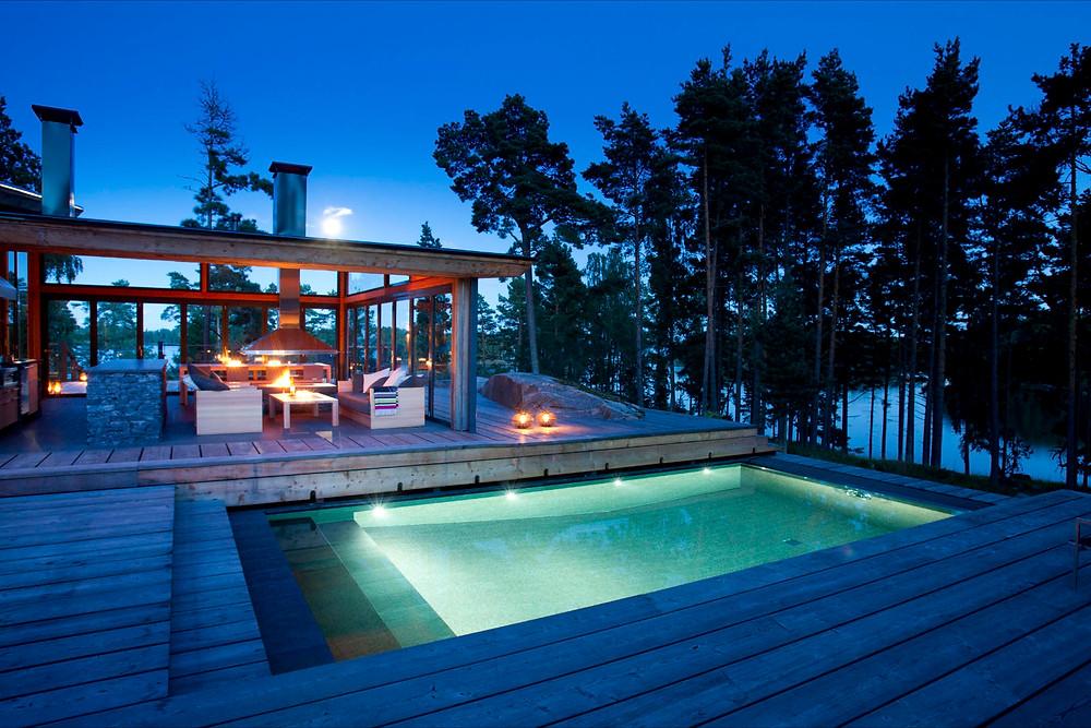 Uima-allas on valaistu kauttaaltaan. Iso harmaa terassi istuu suomalaiseen mökkiympäristöön.